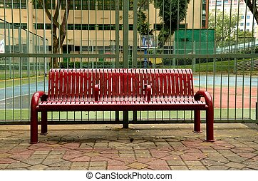 Wet bench outside basketball court - A blood red metal bench...