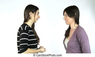 Two happy girlfriends talking