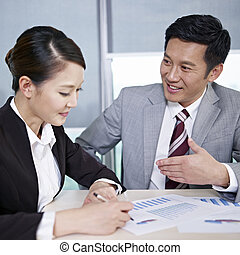 asian business people discussing business in office; focus...