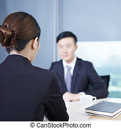 asian business people - rear view of an interviewer talking...