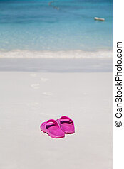 Pink beach bedroom-slippers and traces on sand