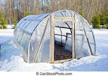 primitive handmade greenhouse in winter time on snow