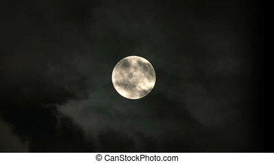 Full Moon - Clouds pass in front of a full moon in a dark...