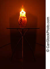 Candle Light - A photograph of a candle on top of a small...