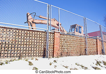industrial place fence and old excavator machine in winter