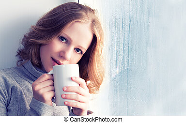 beautiful dreamy young woman with a cup of hot drink coffee at the window in the rain