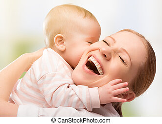 Happy cheerful family. Mother and baby kissing, laughing and...
