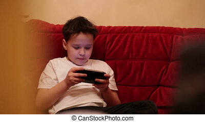 Teenager is playing his portable game console.