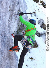 man climbing an ice wall - man in green jacket climbing an...
