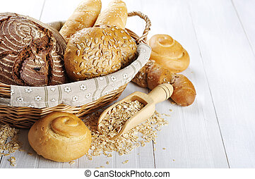 Composition with bread and rolls in wicker basket over white...