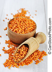Red lentil seeds on a white wooden background