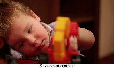 Two year old boy plays with toy trucks.