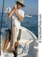 Happy fishermans holds up big redfish - A happy fisherman...