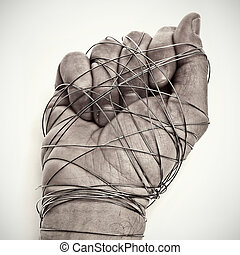 man hand tied with wire, as a symbol of oppression or...