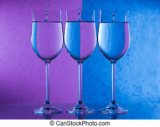 Refraction - three wine glasses with a purple and blue...