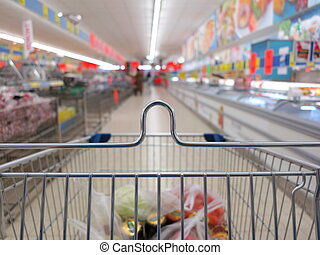view of a shopping cart with grocery items at supermarket...