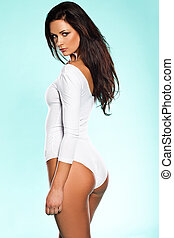 Provocative woman in a white leotard looking back over her...