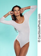 Beautiful slender woman in a white leotard posing with her...