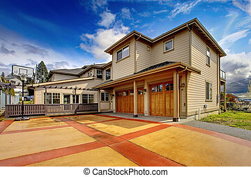 Large New luxury home exterior with orange and red driveway...
