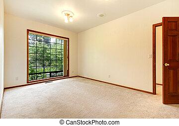 Empty white room with wood door and beige carpet. - Empty...
