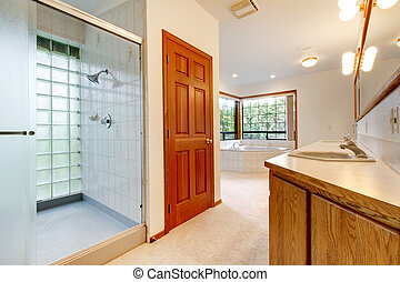 Large white bathroom with tub, shower and wood cabinet.