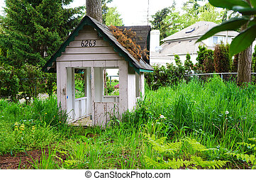 Kids wood play house in the toll grass. Home backyard.