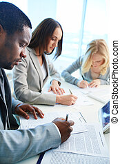 Business education - Confident businessman signing papers...