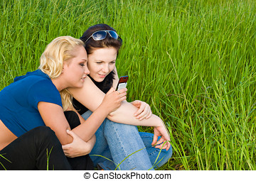 Two women reading sms - Two young women reading sms message...
