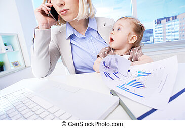 Working with mom - Close-up of businesswoman at workplace...