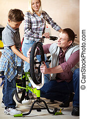 Repairing bike - Portrait of cute boy holding bicycle wheel...