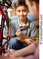 Bike repair service - Portrait of cute boy looking at his...