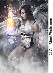 Angel with white wings woman holding a fireball over vintage...