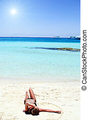 girl lying on white sand beach - Young girl in bikini lying...