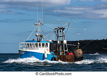 Fishing Trawler - A fishing boat heads out to sea from a...
