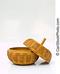A opened yellow wicker basket with a cover isolated on white...