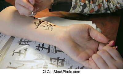 Girl making temporary tatoo on female hand in beauty parlor