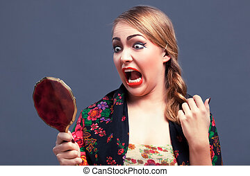 shocked woman in a with mirror - shocked young woman wiht...