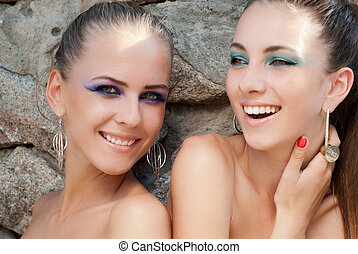 Two happy laughing fashion models - Two young beautiful...