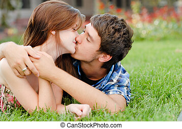 Young happy couple man and woman lying on green lawn and...