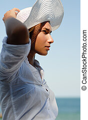 Young woman resting by the sea and wearing white hat bblown...