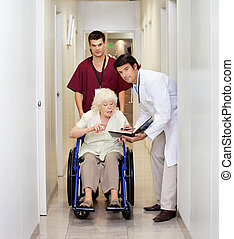 Medical Professionals With Patient In Corridor - Portrait of...