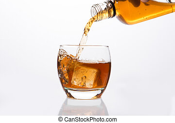 Whisky pouring into glass on white background