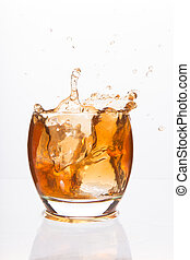 Tumbler glass with brown alcohol on white background