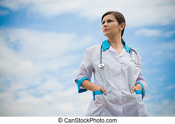 Young successful female doctor on blue sky background -...