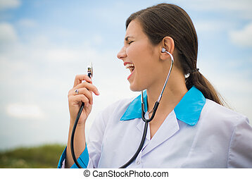 Young female doctor singing in stethoscope - Young happy...