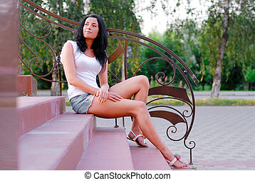 Young beautiful woman sitting on stairs outdoors - Young...