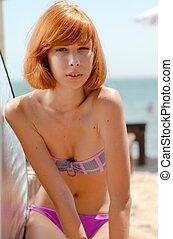 Young beautiful redhead woman in bikini on sea coast - Young...