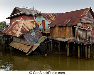 Old wooden house at the canal collapse in Thailand