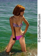 Young beautiful redhead woman in bikini on sea coast...