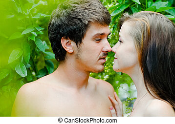 Young happy couple embracing tenderly among green leaves